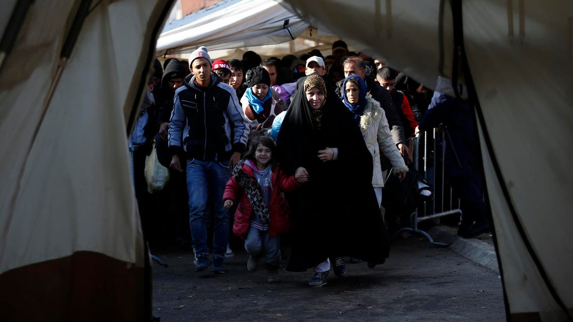 Migrants walk into a tent to register with the police at a refugee center in the southern Serbian town of Presevo, Monday, Nov. 16, 2015.