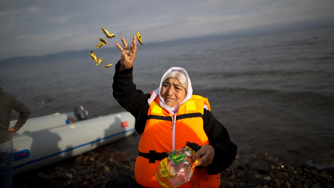 An elderly refugee throws candy in the air shortly after she and other crossed the Aegean sea on a dinghy from the Turkish coast to the Greek island of Lesbos, Tuesday, Nov. 24, 2015. (Reuters)