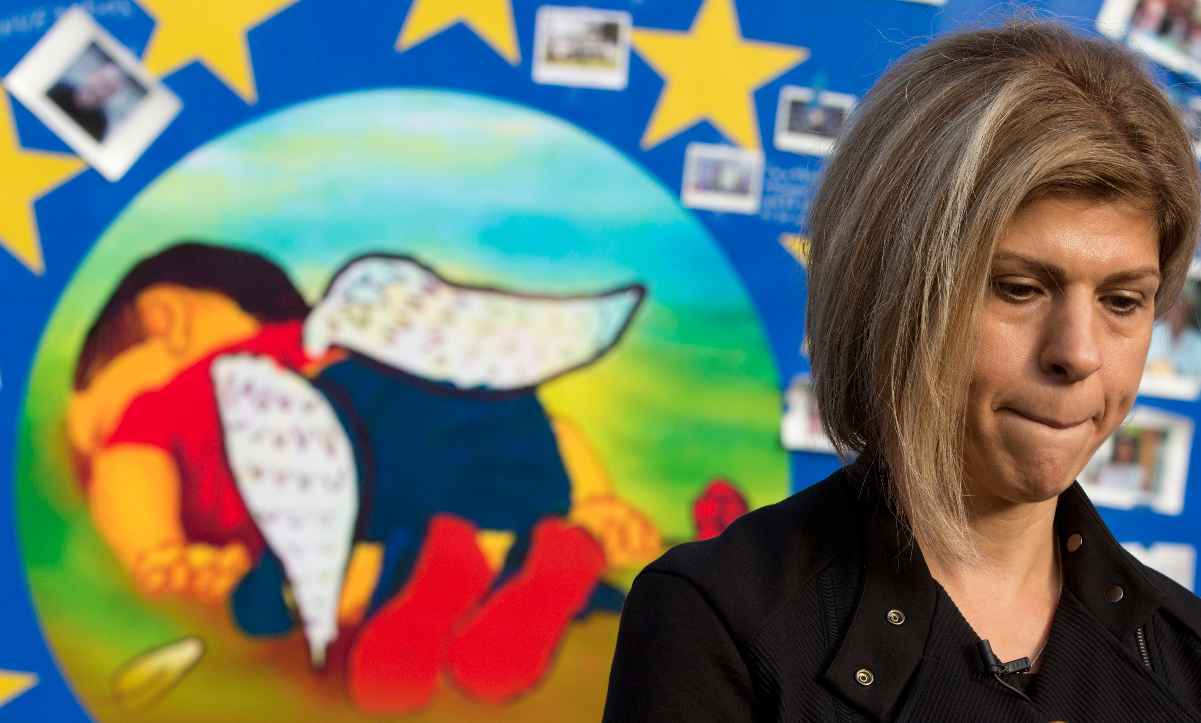 Fatima Kurdi, from Canada, stands next to a painting of her late nephew, Aylan Kurdi, on a board outside of EU headquarters in Brussels on Monday, Sept. 14, 2015.
