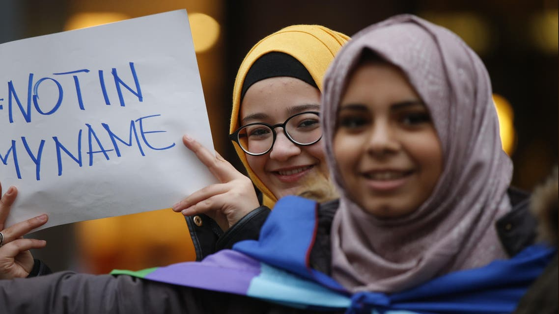 """Women hold a placard during a demonstration called """"Not in my name"""" of Italian muslims against terrorism, in downtown Rome. (AP)"""