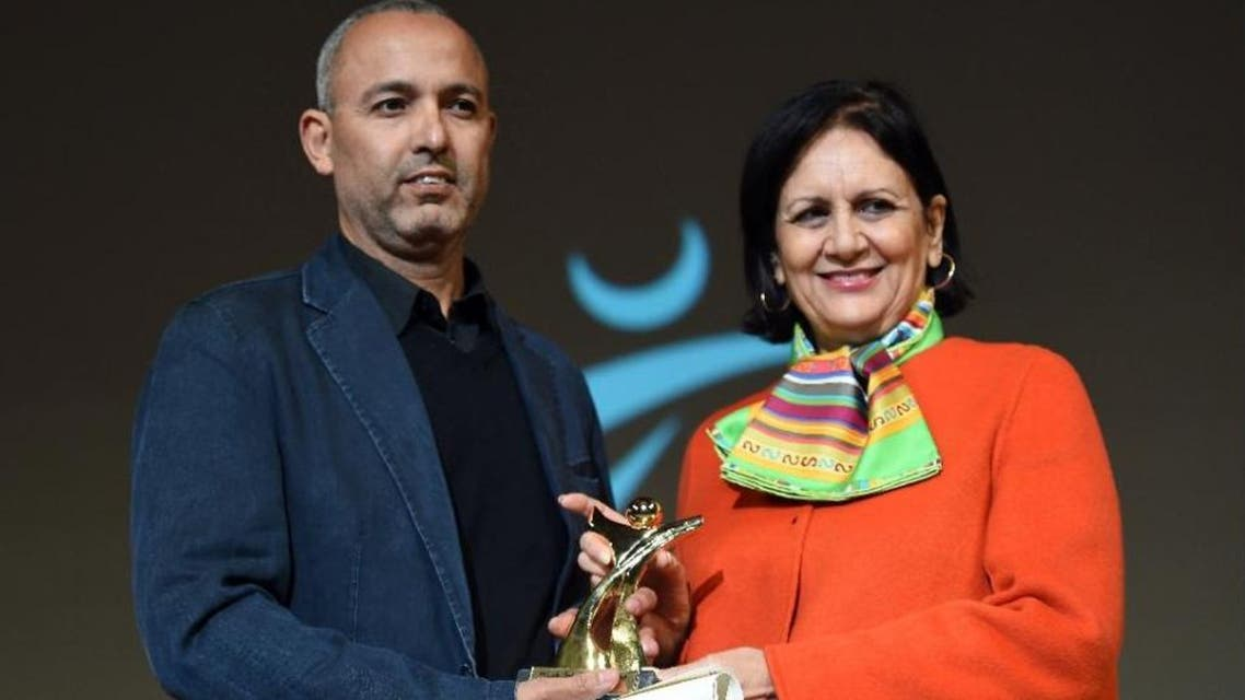 """Moroccan director Mohamed Mouftakir (L) receives from Tunisian Culture Minister Latifa Lakhdar the Golden Tanit award for his film L'orchestre des aveugles"""" during the 26th Carthage Film Festival on November 28, 2015 in tunisian capital Tunis"""