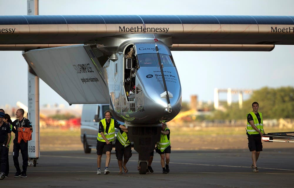 In this July 3, 2015, file photo, ground crew push the Solar Impulse 2, a solar powered airplane, towards the hangar after landingat the Kalaeloa Airport in Kapolei, Hawaii. The Solar Impulse team said in a news release early Wednesday, July 15, 2015, that they are suspending the around-the-world journey in Hawaii, after the plane suffered battery damage during its flight to the islands. The team will continue the attempt, but irreversible damage caused by overheating batteries has grounded the flight until at least April. (AP Photo/Marco Garcia, File)