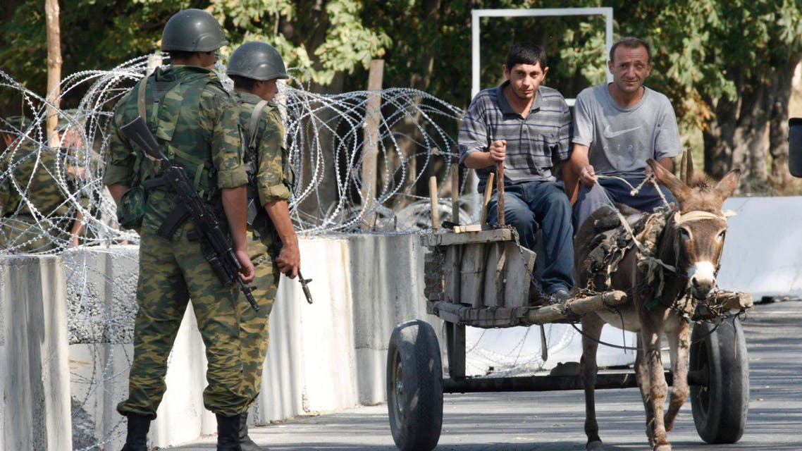 Two people ride a cart past Russian soldiers at a Russian checkpoint at Karaleti, 7 km (4 miles) northwest of Gori, Georgia, on Wednesday, Sept. 3, 2008. The checkpoint is part of a Russian military presence in the so-called security zone that Moscow claimed for itself in the Georgian territory after last month's war. (AP Photo/Shakh Aivazov)