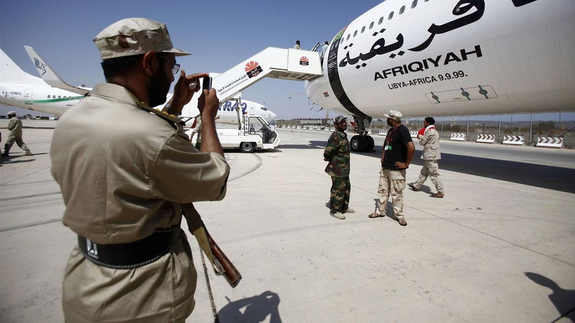 A Libyan rebel fighter takes souvenir photographs of fellow fighters standing beside one of Muammar Qaddafi's private plane at the international airport in Tripoli. (File photo: Reuters)