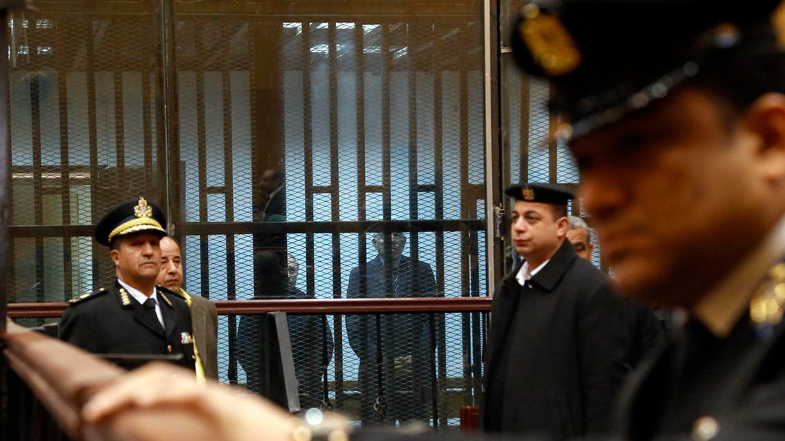 Former Egyptian Prime Minister Ahmed Nazif, right in cage, and former Interior Minister Habib el-Adly, stand behind bars in a courtroom during a retrial hearing that acquitted them over charges of squandering public money in Cairo, Egypt, Tuesday, Feb. 24, 2015. The case stems from allegations they collaborated in awarding a German firm a contract to import license plates by direct order. Over the past months, many Mubarak-era officials have won a series of acquittals, mostly in corruption-related cases. (AP Photo/El Shorouk, Aly Hazzaa) EGYPT OUT