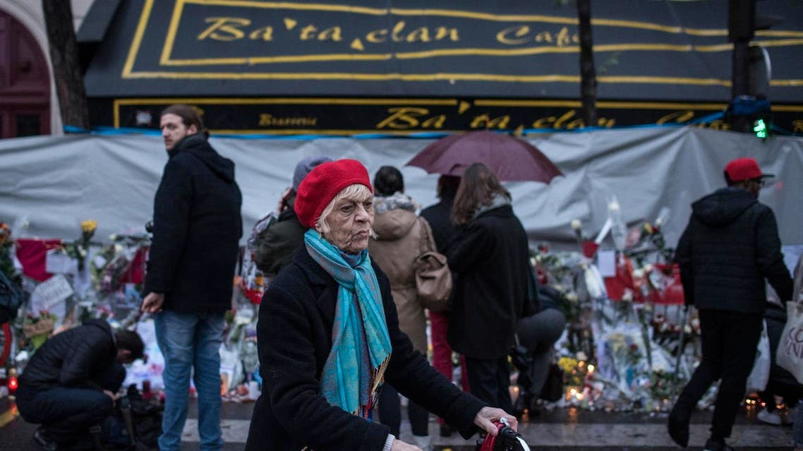 A woman walks as people pay respects to victims of the Paris attacks in front of the Bataclan concert hall on Nov. 25, 2015, in Paris. (AP)