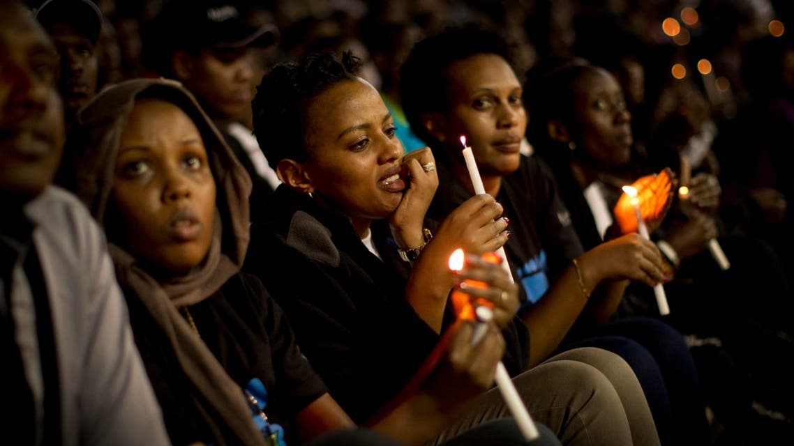 Rwandans light candles of remembrance and listen to religious speeches and music at an evening ceremony at the Amahoro stadium in Kigali, Rwanda Monday, April 7, 2014. Sorrowful wails and uncontrollable sobs resounded Monday as thousands of Rwandans packed the country's main sports stadium to mark the 20th anniversary of the beginning of a devastating 100-day genocide. (AP Photo/Ben Curtis)
