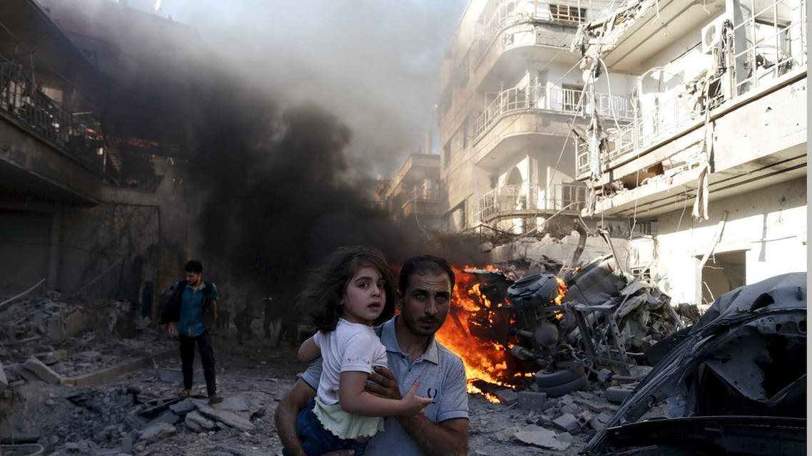 A man carries a girl as they rush away from a site hit by what activists said were airstrikes by forces loyal to Syria's President Bashar al-Assad in the Douma neighbourhood of Damascus, Syria August 24, 2015. REUTERS/Bassam Khabieh SEARCH - PICTURES OF THE YEAR 2015 - FOR ALL IMAGES TPX IMAGES OF THE DAY