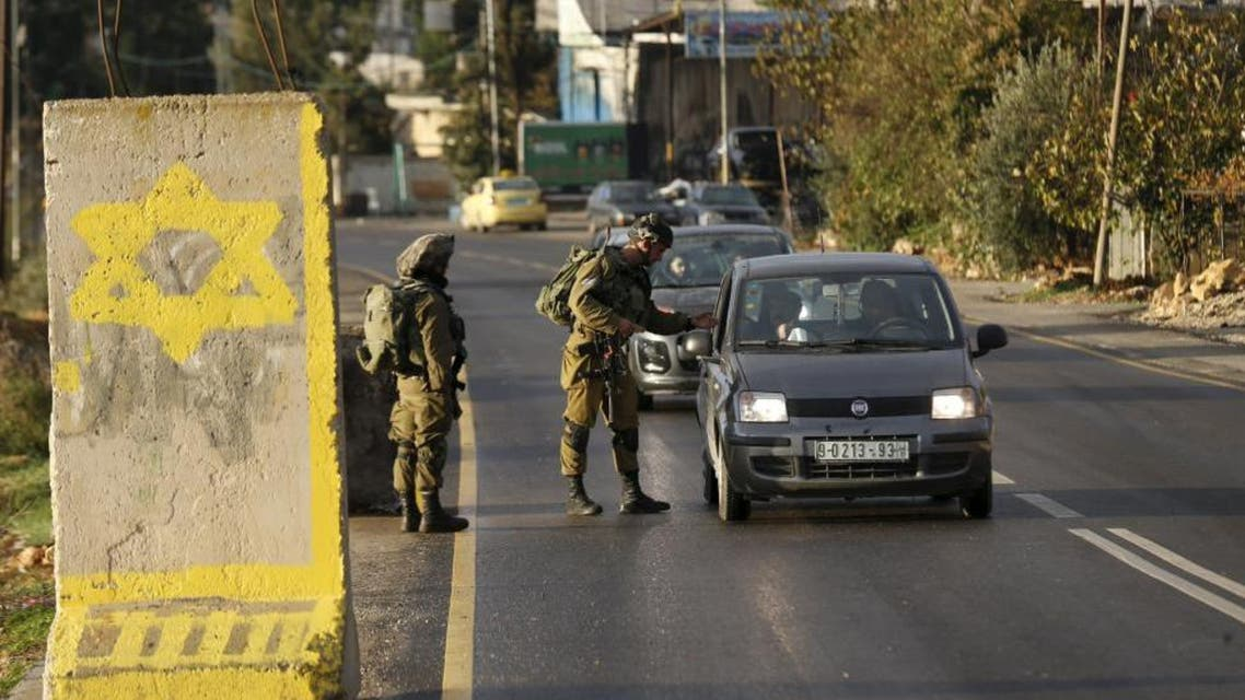 Israeli soldiers check Palestinian cars at a checkpoint at the entrance to the village of Halhul near the West Bank city of Hebron. (Reuters)