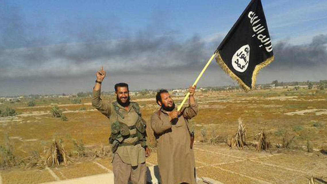FILE - In this file photo released on Sunday, June 28, 2015, by a website of Islamic State militants, an Islamic State militant waves his group's flag as he and another celebrate in Fallujah, Iraq, west of Baghdad.The Islamic State's gruesome rampage across the Middle East has united the world in horror but left it divided over how to refer to the group, with observers adopting different acronyms based on their translation of an archaic geographical term and the extent to which they want to needle the group. (Militant website via AP, File)