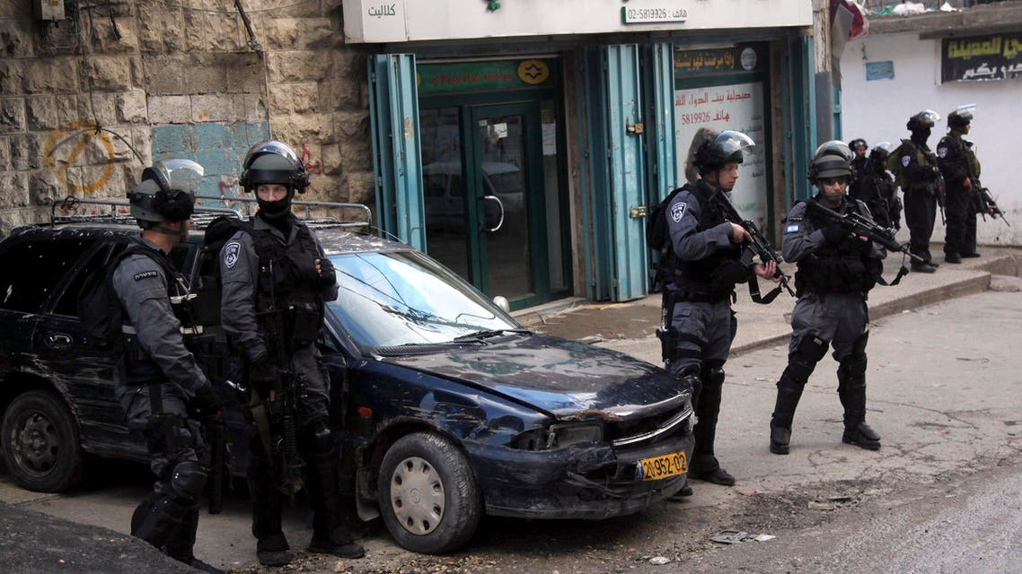 Israeli policemen stand guard in the Palestinian refugee camp Shuafat in Jerusalem, Wednesday Dec. 2, 2015.