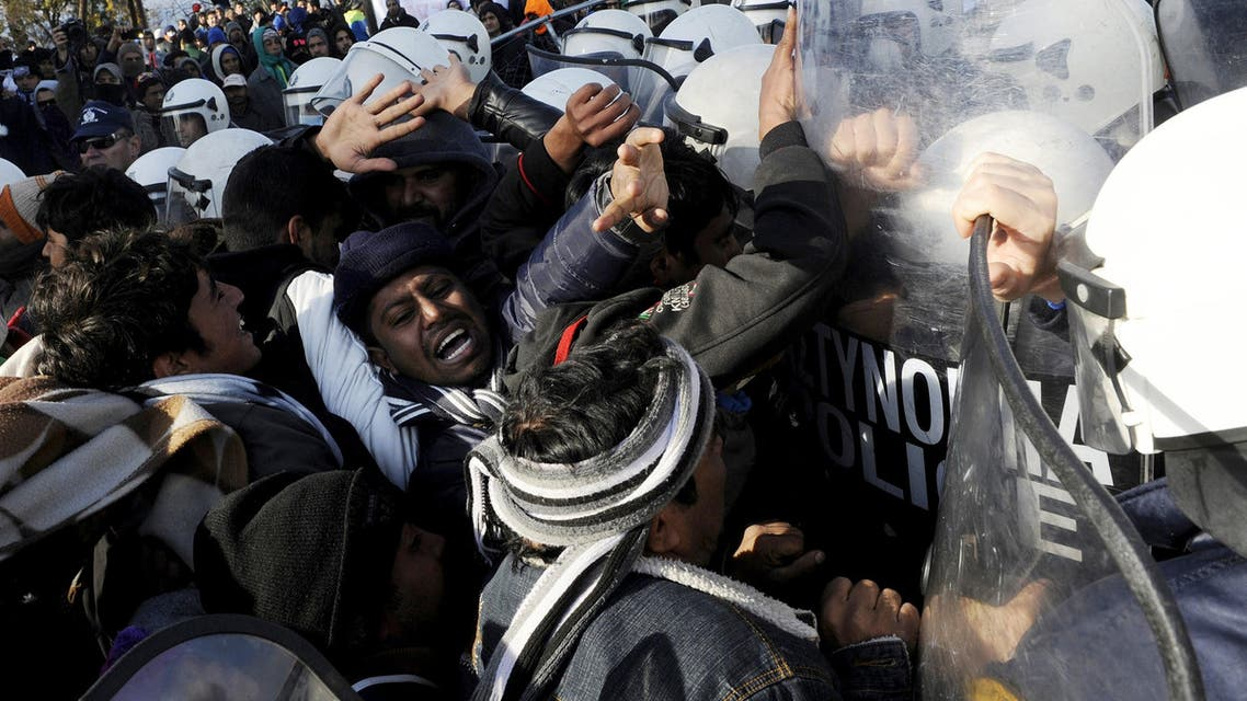 Stranded migrants scuffle with Greek police officers as they try to cross the Greek-Macedonian border, near the village of Idomeni, Greece December 2, 2015.