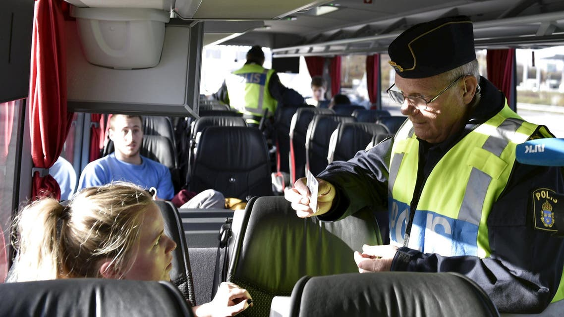 A police officer checks passports inside a bus at Lernacken, on the Swedish side of the Oresund strait, November 12, 2015. (Reuters)