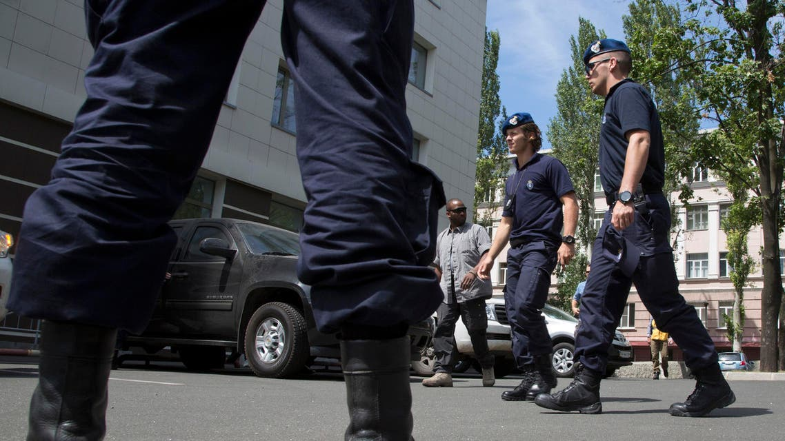Dutch policemen walk to a hotel in as they returned to Donetsk from Shakhtarsk, Donetsk region, eastern Ukraine Monday, July 28, 2014 after failing to reach a place of Malaysia Airlanes plane crash. Heavy fighting raged Monday around the Malaysia Airlines debris field, once again preventing an international police team charged with securing the site from even getting there. (AP Photo/Dmitry Lovetsky)