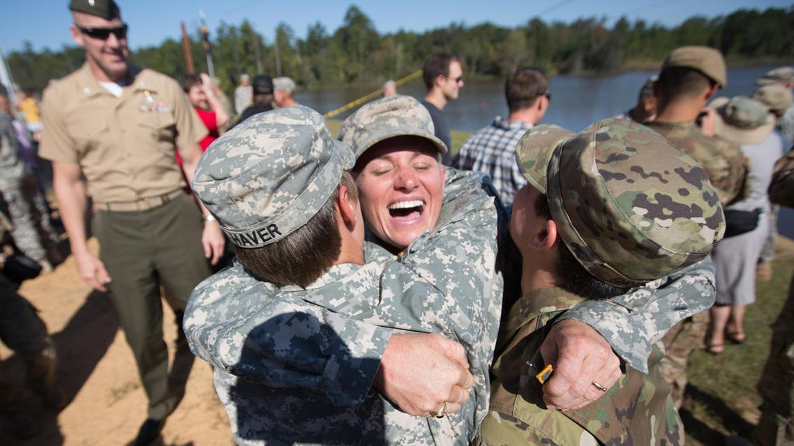 Maj. Lisa Jaster, center, embraces First Lt. Shaye Haver, left, and U.S. Army Capt. Kristen Griest, right, after an Army Ranger School graduation ceremony, Friday, Oct. 16, 2015, in Fort Benning, Ga. Jaster, who is the first Army Reserve female to graduate the Army's Ranger School, joins Griest and Haver as the third female soldier to complete the school. (AP Photo/Branden Camp)