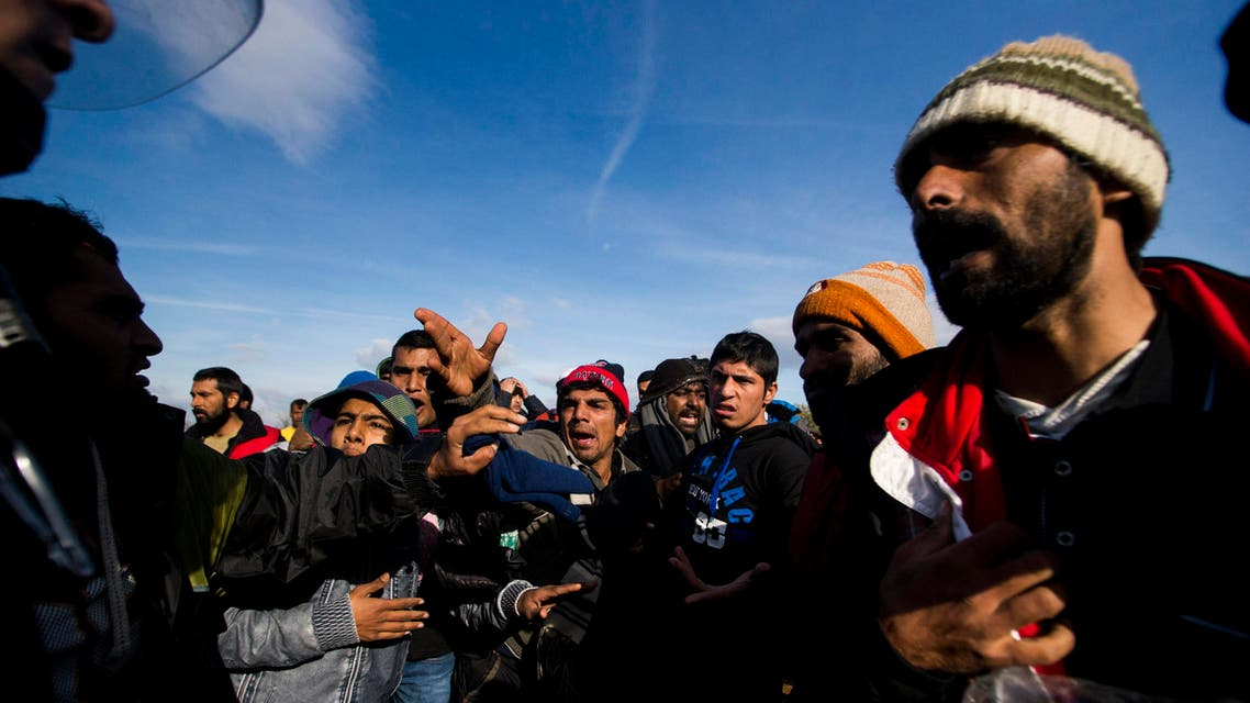 Migrants argue with Macedonian policemen at the Macedonia-Greece border at the city of Idomeni, Greece, Wednesday Dec. 2, 2015. Macedonia has stopped allowing people from any country other than those facing war, and leaving some hundreds of people unable to cross the border from Greece. (Zoltan Balogh/MTI via AP)