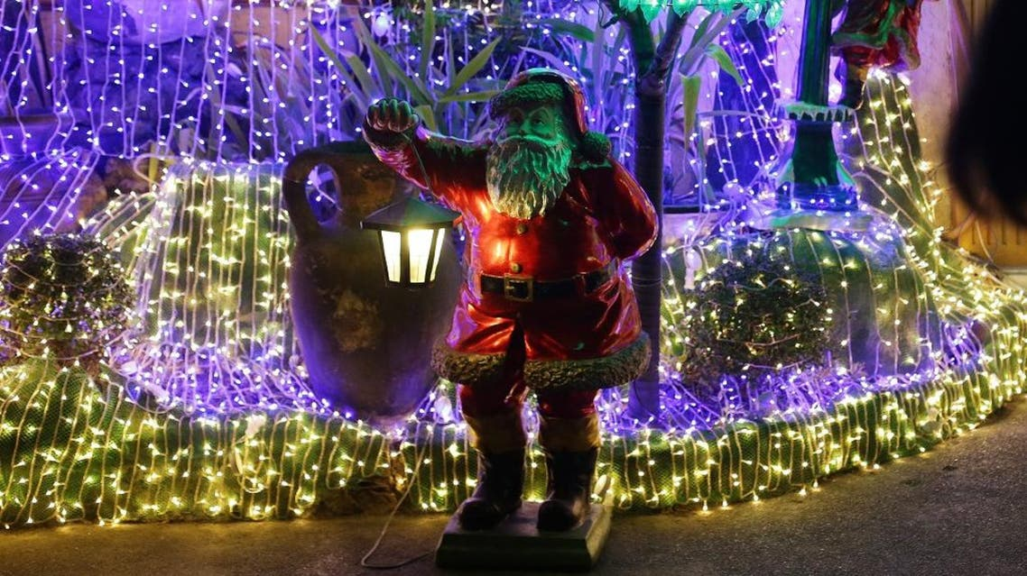 a Filipino woman passes by Christmas decorations outside a house in Cainta, Rizal province, east of Manila, Philippines. (AP)