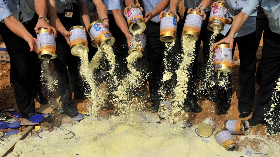 Staff members of the local quality supervision bureau empty tainted milk powder packets at a garbage dump site in Shenzhen, Guangdong province September 19, 2008. (Reuters)