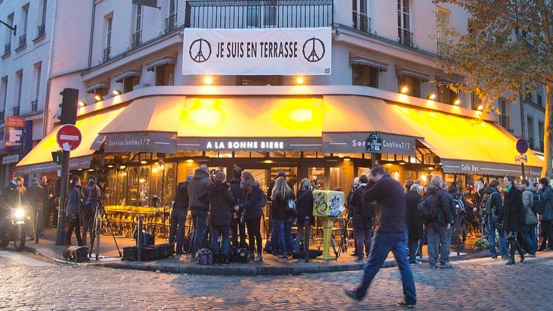 People gather around La Bonne Biere cafe in Paris during its reopening Friday, Dec. 4, 2015. The cafe where five people were killed by a squad of Islamic extremist gunmen on Nov. 13, terrorizing central Paris reopened for business Friday. (AP Photo/Jacques Brinon)