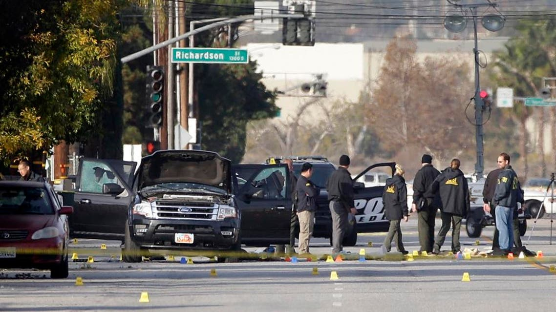 Investigators gather around a Black SUV that was involved in Wednesday's police shootout with suspects, Thursday, Dec. 3, 2015, in San Bernardino, Calif. A heavily armed man and woman dressed for battle opened fire on a holiday banquet for his co-workers Wednesday, killing multiple people and seriously wounding others in a precision assault, authorities said. Hours later, they died in a shootout with police. (AP Photo/Jae C. Hong)