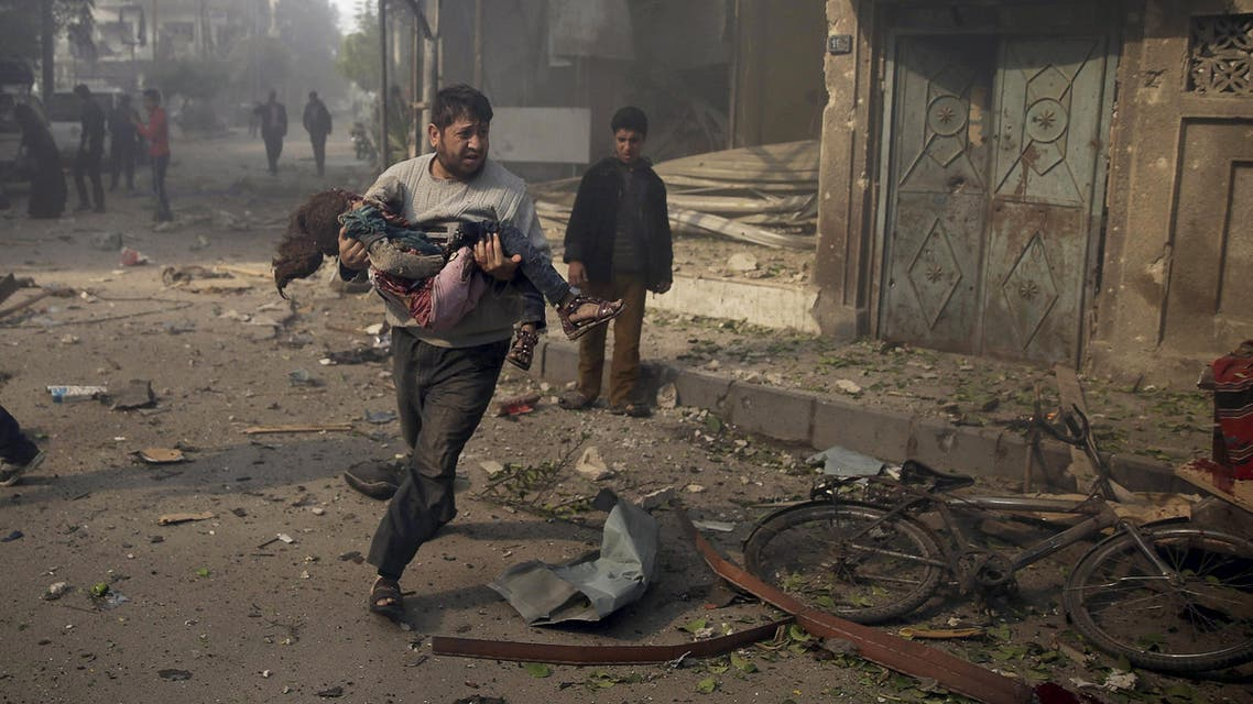 A man carries an injured girl as he rushes away from a site hit by what activists said were airstrikes by forces loyal to Syria's President Bashar al-Assad, in the Douma neighborhood of Damascus, Syria November 7, 2015. REUTERS