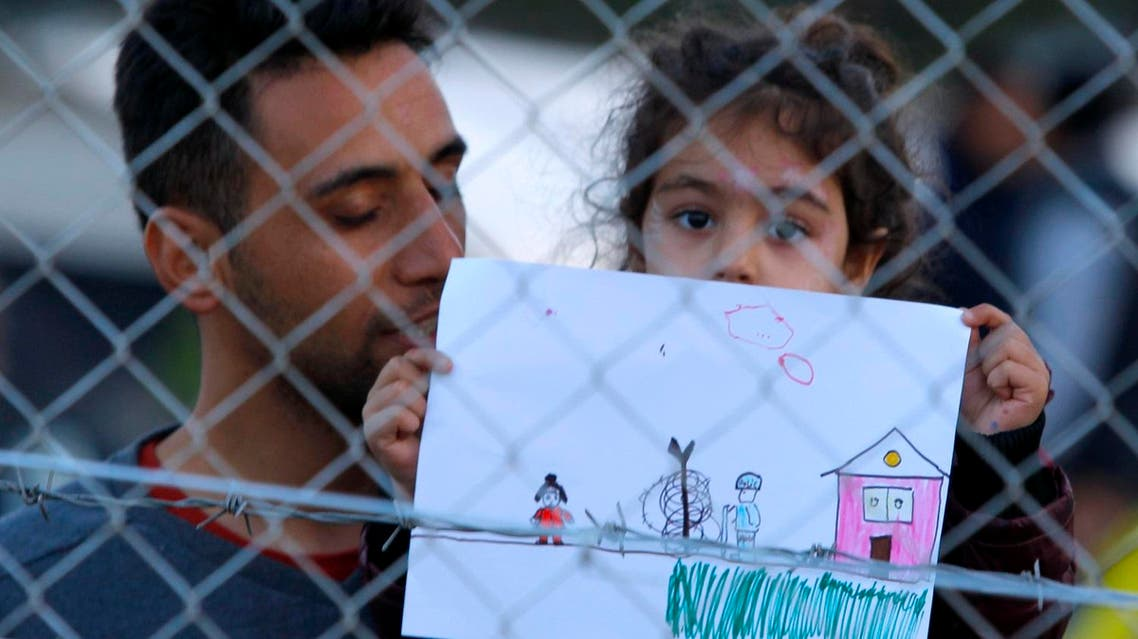 A young migrant girl holds up a drawing in a makeshift camp on the Macedonian-Greek border, near Gevgelija, Macedonia. (Reuters)