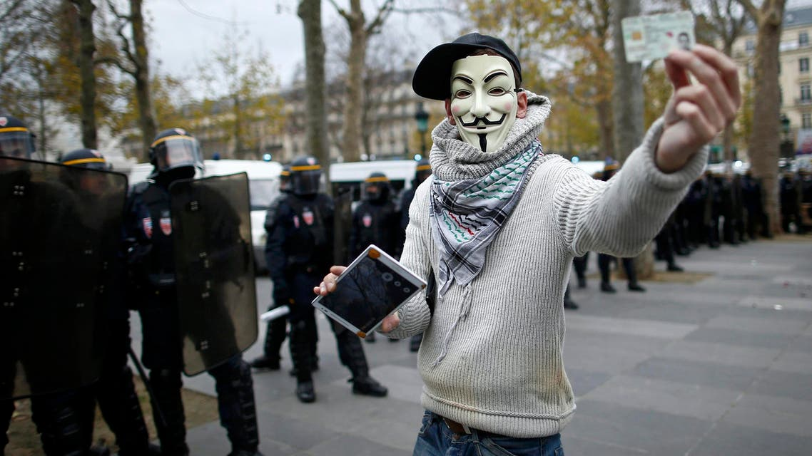 An anonymous activist wears a Guy Fawkes mask at a demonstration near French CRS police before clashes at the Place de la Republique after the cancellation of a planned climate march following shootings in the French capital, ahead of the World Climate Change Conference 2015 (COP21), in Paris, France, November 29, 2015.