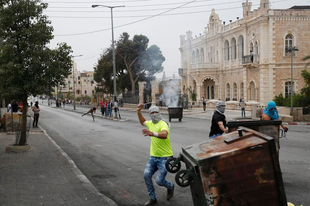 This Friday, Oct. 23, 2015 photograph shows Palestinians clashing with Israeli troops in front of the Intercontinental hotel in the West Bank city of Bethlehem. The century-old Jacir Palace hotel, with its soaring stone archways and wrought iron balconies, was once a symbol of Bethlehem's wealth and tourism potential. Today, the property reflects the city's dour mood ahead of the crucial Christmas season after months of unrest that has taken more than 100 lives, including a Palestinian waiter from the hotel. (AP Photo/Nasser Shiyoukhi)