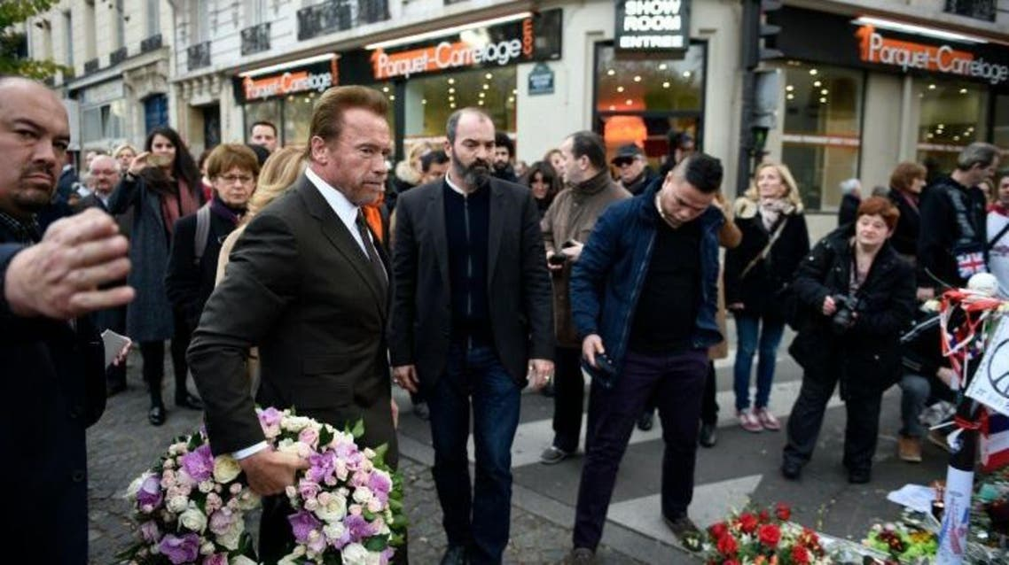 Former governor of California and film star Arnold Schwarzenegger arrives to pay his respects at a memorial outside the Bataclan concert hall on December 5, 2015 in Paris | AFP