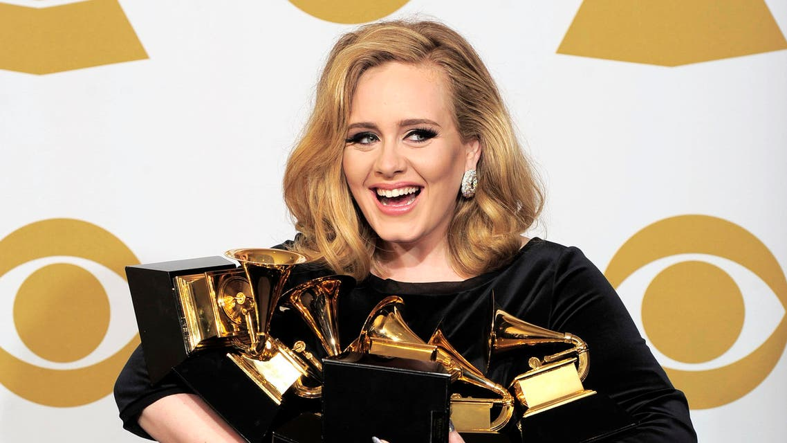 """Adele poses backstage with her six awards at the 54th annual Grammy Awards on Sunday, Feb. 12, 2012 in Los Angeles. Adele won awards for best pop solo performance for """"Someone Like You,"""" song of the year, record of the year, and best short form music video for """"Rolling in the Deep,"""" and album of the year and best pop vocal album for """"21."""" (AP Photo/Mark J. Terrill)"""