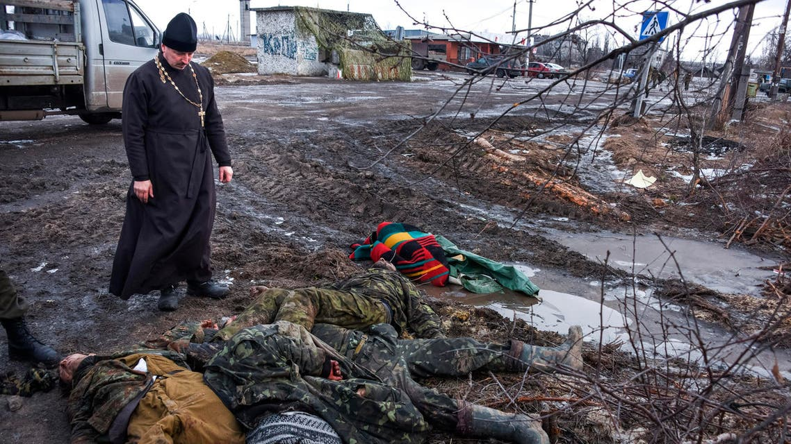 FOR USE AS DESIRED, YEAR END PHOTOS - FILE - An Orthodox priest stands next to the bodies of killed Ukrainian soldiers on a check-point captured by pro-Russian rebels at the town of Krasniy Partizan, eastern Ukraine, Saturday, Jan. 24, 2015. The fighting continues despite several cease fire declarations. (AP Photo/Mstyslav Chernov, File)