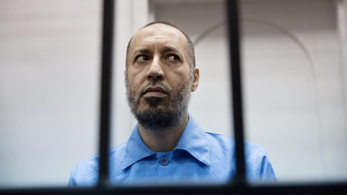 Saadi Muammar Gadhafi, wears a blue jumpsuit behind bars during his trial in the center of Tripoli, Libya, Sunday, Nov. 1, 2015. He is charged with the first-degree murder in 2005 of a former trainer at Tripoli's Al-Ittihad football club. (AP Photo/Mohamed Ben Khalifa)