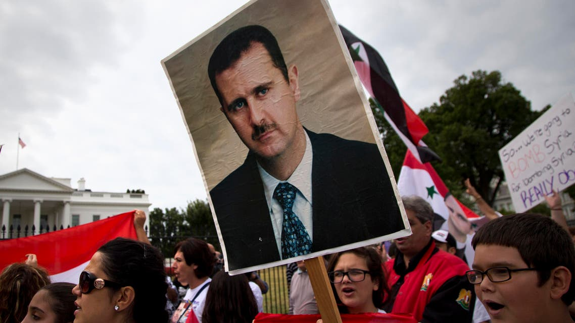 Protesters carry an image of Syrian President Bashar Hafez al-Assad during a demonstration against US military action in Syria, Monday, Sept. 9, 2013.
