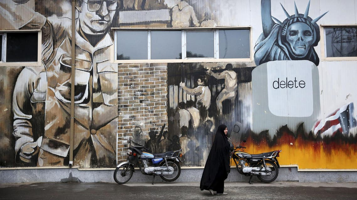 """An unidentified woman walks under an anti-U.S. graffiti painted on the walls of the former U.S. Embassy in Tehran, Iran, Saturday, Nov. 2, 2013. Iran's hardliners unveiled two new """"Death to America"""" songs at the site of the former U.S. embassy in Tehran Saturday to keep the anti-U.S. sentiments alive. The live performance Saturday is a warm-up to the main event: A major anti-U.S. rally on Monday marking the Nov. 4 anniversary of the U.S. embassy takeover in 1979 by militant students. The event is marked every year with protests outside the compound's brick walls. (AP Photo/Ebrahim Noroozi)"""