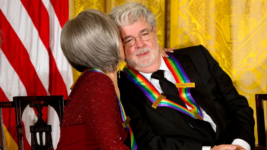 Actress and singer Rita Moreno, left, kisses filmmaker George Lucas on the cheek, as the 2015 Kennedy Center Honors honorees listen to President Barack Obama speak at the 2015 Kennedy Center Honors reception in the East Room of the White House in Washington, Sunday, Dec. 6, 2015. (AP)
