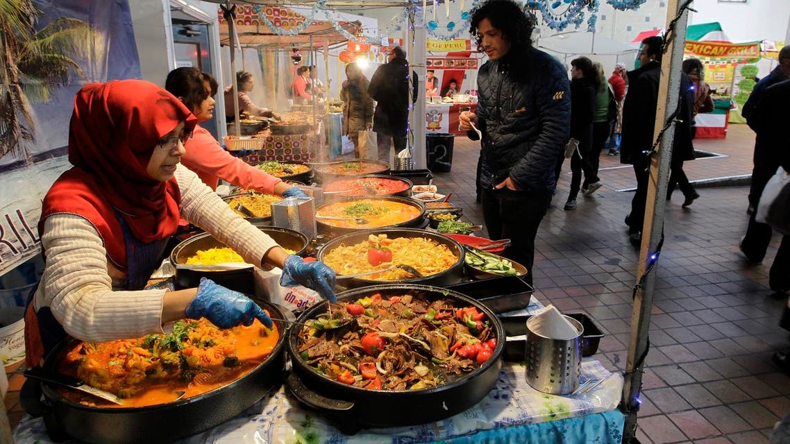a man is being served at a food stall on Brick Lane in east London. (AP)