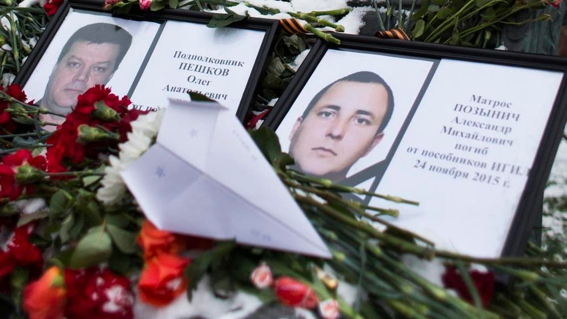 Photos of Lt.Col. Oleg Peshkov, left, and sailor Alexander Pozynich are placed at a monument to Soviet Officers with flowers and a toy jet made of paper outside Russian Army General Staff headquarters in Moscow, Russia, Thursday, Nov. 26, 2015. Peshkov was a pilot of Russian Su-24, which was shot down by Turkish air forces and Pozynick took part in a rescue operation, both were killed. (AP Photo/Ivan Sekretarev)