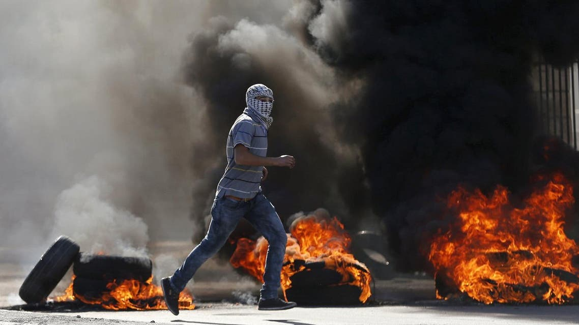 A Palestinian protester runs in front of burning tyres during clashes with Israeli troops in the West Bank city of Bethlehem. (File photo: Reuters)