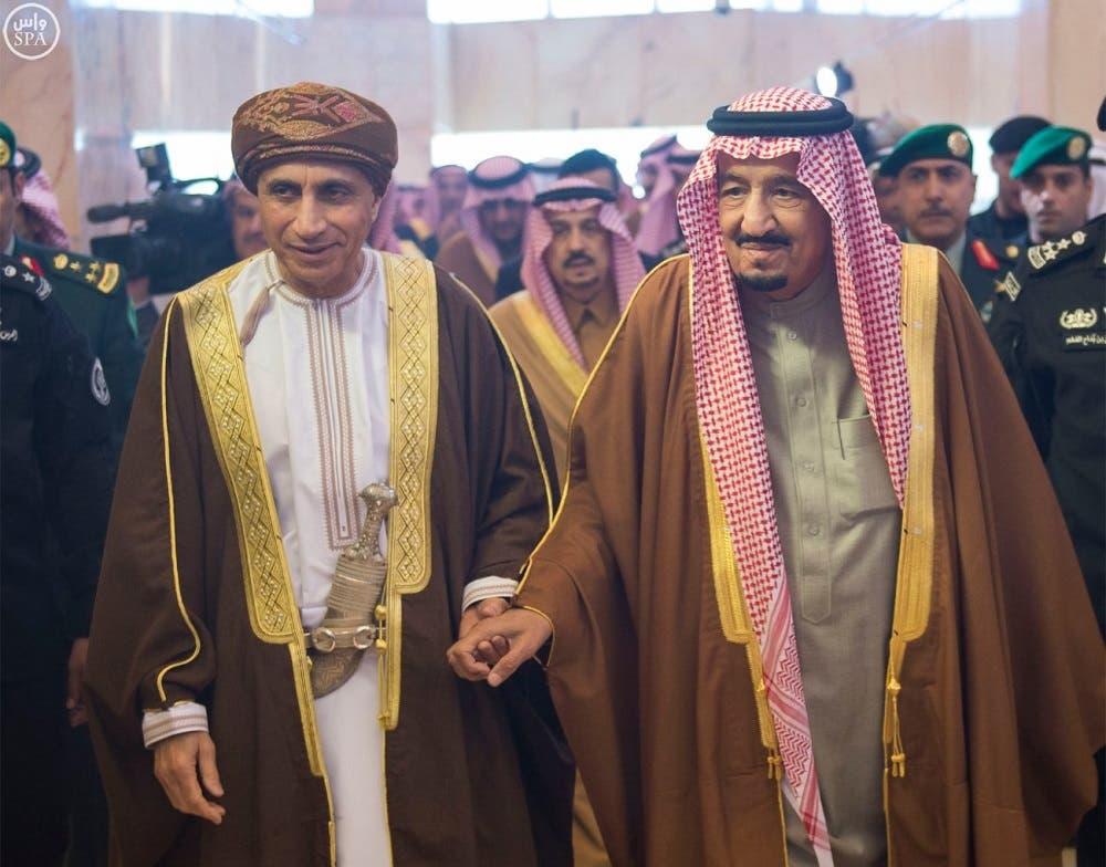 Saudi King Salman bin Abdulaziz walks with Oman Deputy Prime Minister Sayyid Fahd bin Mahmoud al Saidm (SPA)
