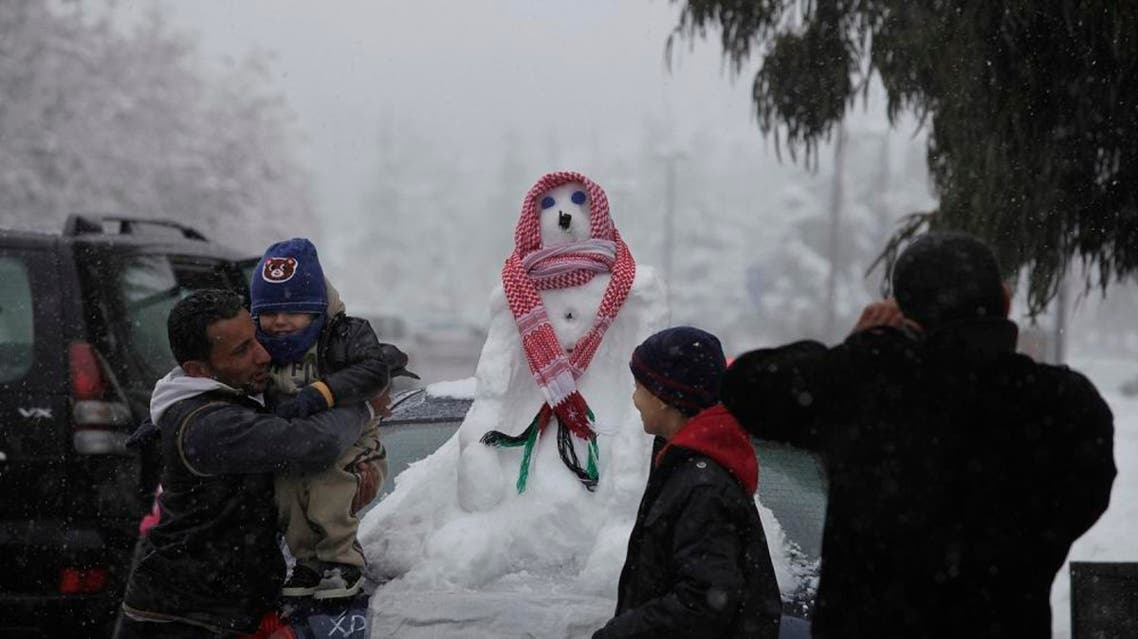 Jordanians take photos with a snowman rapped with a traditional scarf during a snowstorm in Amman, Dec. 2013. (File photo: AP)