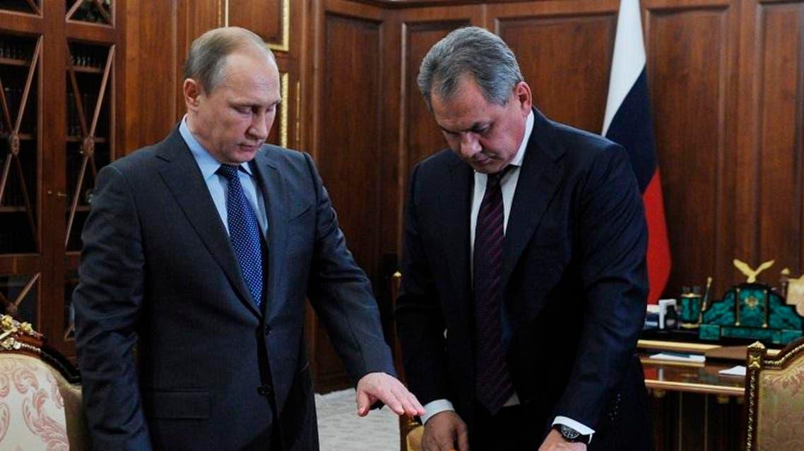Russian President Vladimir Putin, left, and Defense Minister Sergei Shoigu, examine a flight recorder from the Russian warplane shot down by a Turkish jet on Nov. 24. (AP)