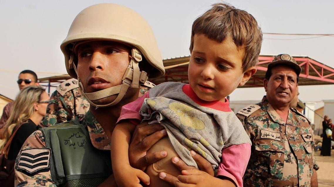 A Jordanian soldier carries a Syrian child arriving in Jordanian territory in the Roqban reception point near the northeastern Jordanian border with Syria. (File photo: AP)