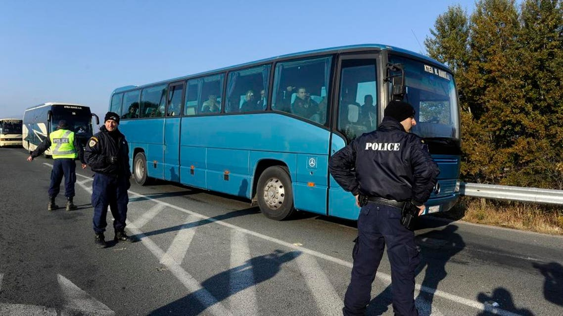 Greek police officers direct buses carrying hundreds of migrants, who were stranded on the Greek-Macedonian border and blocked rail traffic, after a police operation near the village of Idomeni, Greece, December 9, 2015. REUTERS