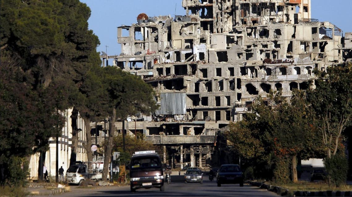 Vehicles drive in front of damaged buildings near the new clock square in the old city of Homs. (Reuters)