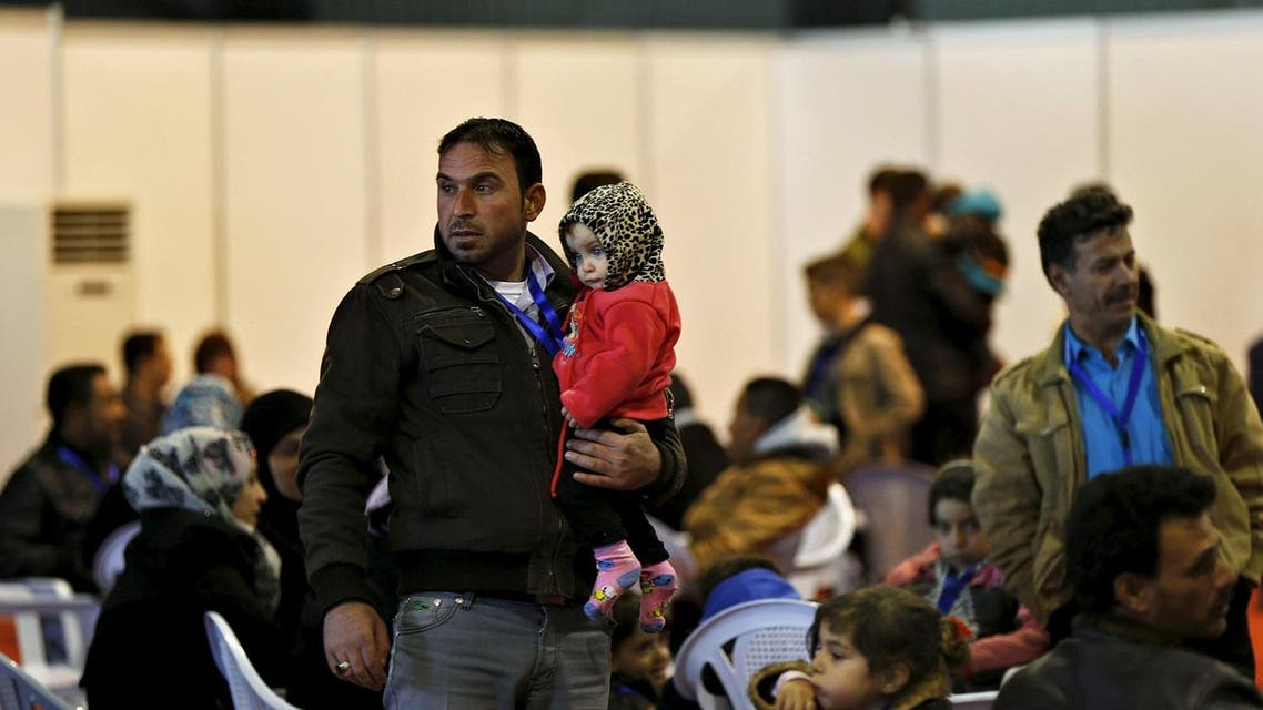 A Syrian refugee carries his daughter as he waits to registers his family's information at the Canadian processing centre for Syrian refugees. (Reuters)