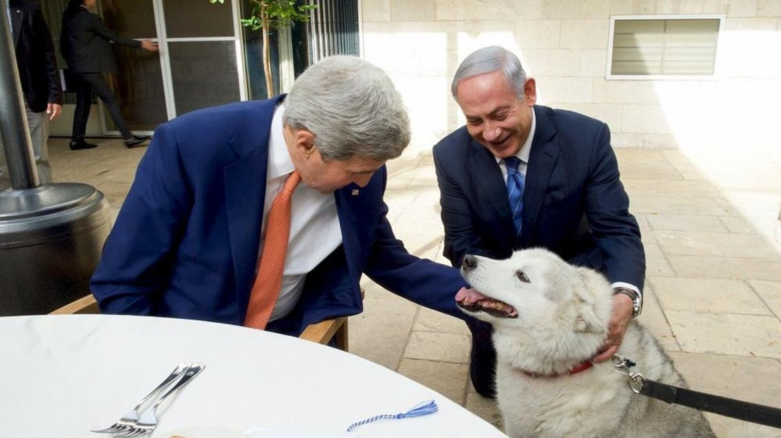 Israeli Prime Minister Benjamin Netanyahu (R) shows U.S. Secretary of State John Kerry his recently adopted dog Kaiya, during their meeting in Jerusalem November 24, 2015. | Reuters