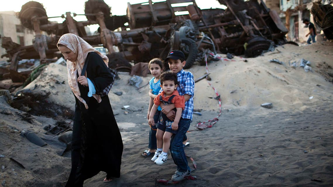 In this photo taken Sunday, May 22, 2011, a family walks next to destroyed vehicles in Tripoli Street, the center of fighting between forces loyal to Libyan leader Moammar Gadhafi and rebels in downtown Misrata, Libya.