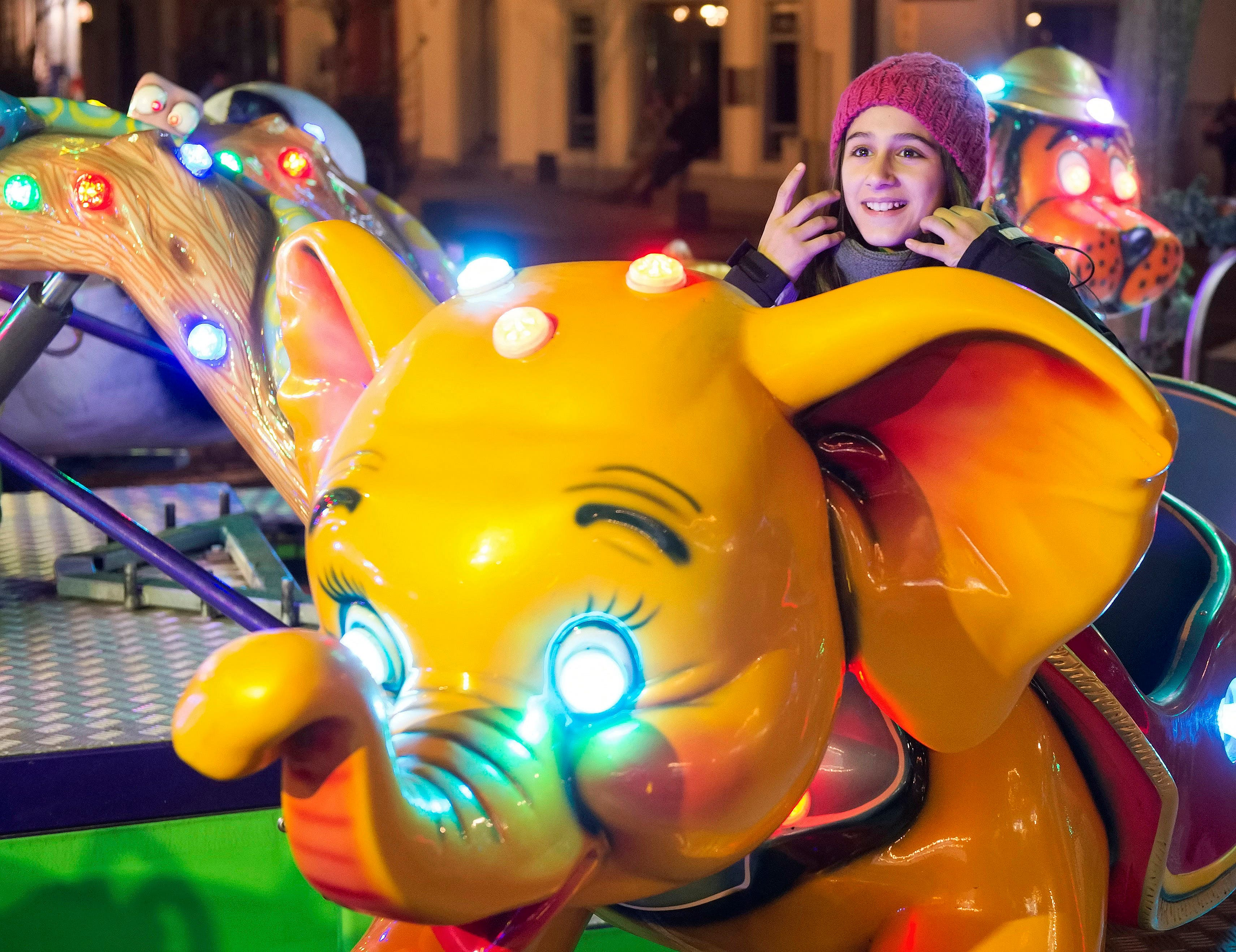 In this photo taken Tuesday, Dec. 8, 2015, Syrian refugee Raghad Habashieh rides on a carousel at the Christmas market in Zwickau, eastern Germany.