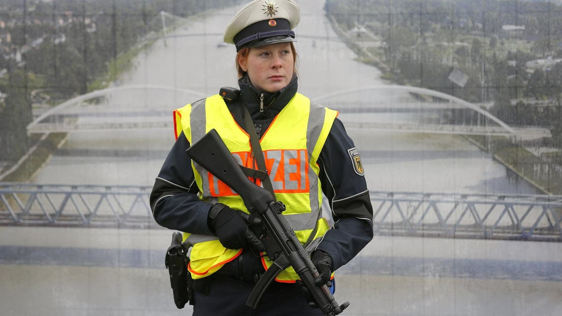 A German police officer stands in front of a poster with a picture of the Rhein river as she takes part in a security control at the French-German border in Strasbourg, France, November 28, 2015. (Reuters)