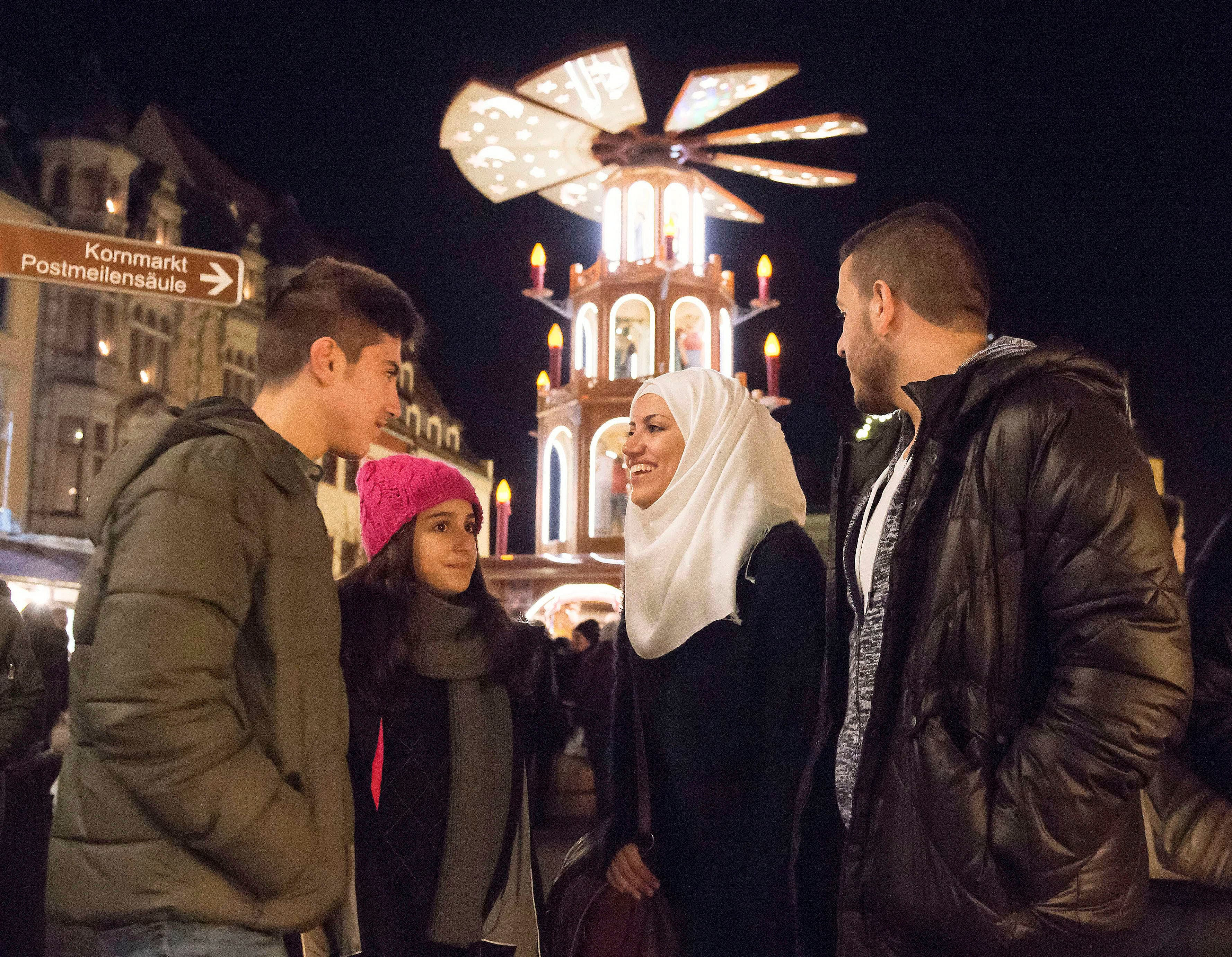 In this photo taken Tuesday, Dec. 8, 2015, Syrian refugees Yaman Habashieh, Raghad Habashieh, Reem Habashieh and Mohammed Habashieh, from left to right, visit the Christmas market in front of a wooden traditional pyramid in Zwickau, eastern Germany.